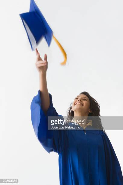 Hispanic female graduate throwing cap