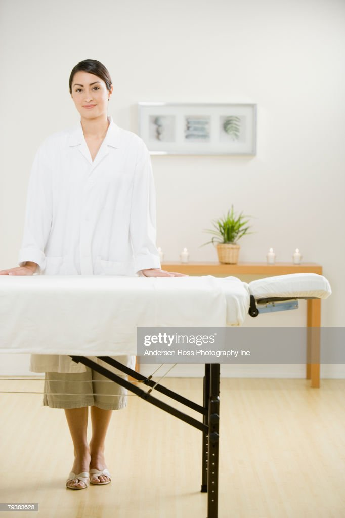 Hispanic female massage therapist next to massage table : Stock Photo