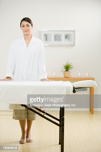 Hispanic female massage therapist next to massage table : Stock-Foto