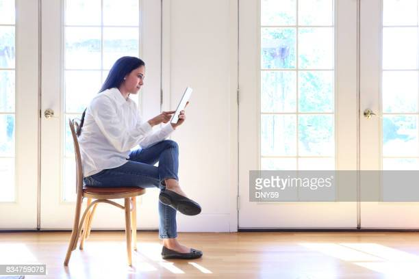 Hispanic Female Millennial Using Digital Tablet While Working At Home