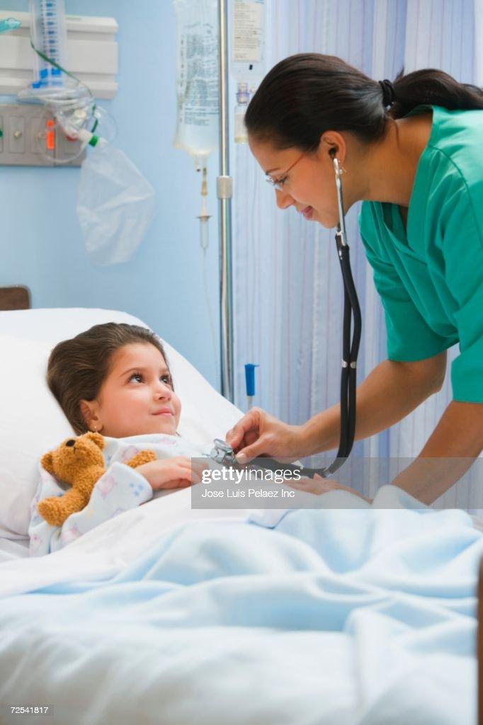 Hispanic female nurse using stethoscope on girl in hospital bed : Stock Photo
