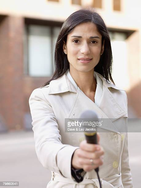 Hispanic female reporter holding microphone