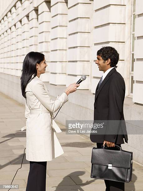 Hispanic female reporter interviewing businessman