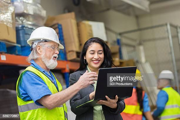 Hispanic female supervisor talking with senior warehouse worker