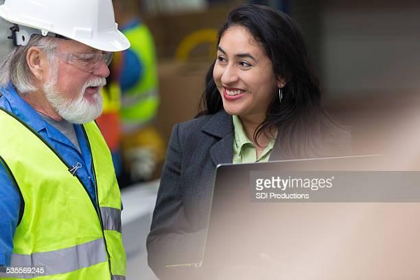 ヒスパニック女性の倉庫スーパーバイザーに話しをする老人ブルーのカラーの労働者