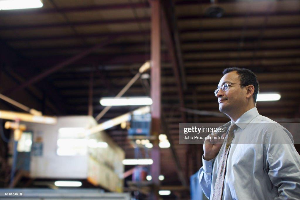 Hispanic foreman standing in factory : Stock Photo