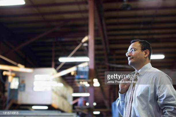 Hispanic foreman standing in factory