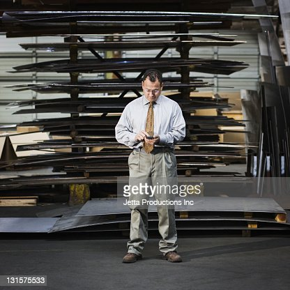 Hispanic foreman using cell phone in factory : Stock Photo