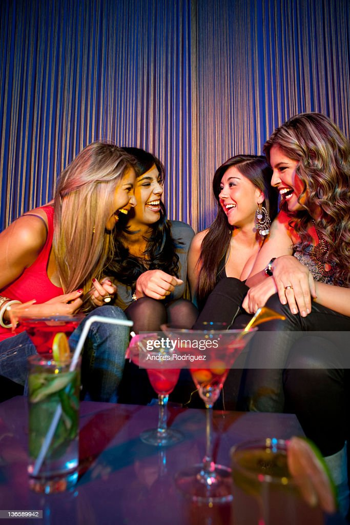 Hispanic friends drinking cocktails in bar