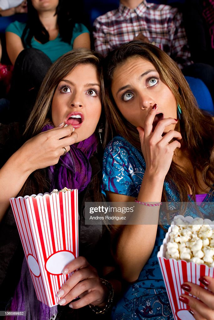 Hispanic friends enjoying popcorn in movie theater : Stock Photo