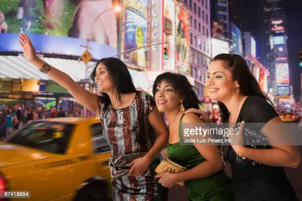 Hispanic friends hailing taxi cab