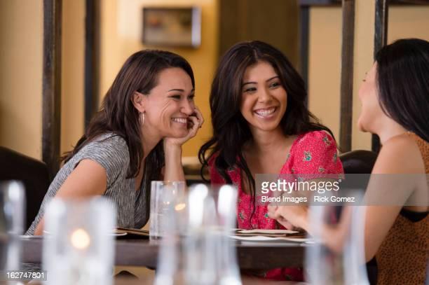 Hispanic friends having dinner in restaurant