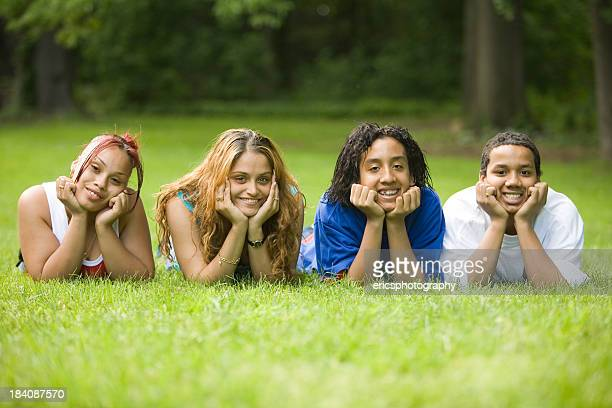 Hispanic friends lying on the lawn