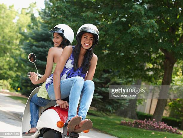 Hispanic friends riding scooter together