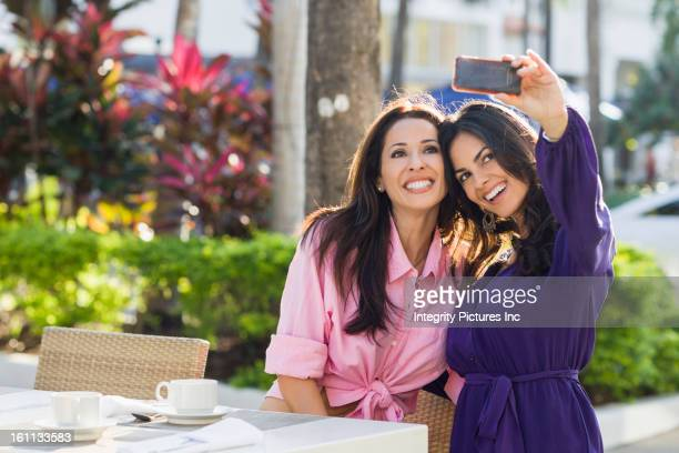 Hispanic friends taking self-portrait with cell phone