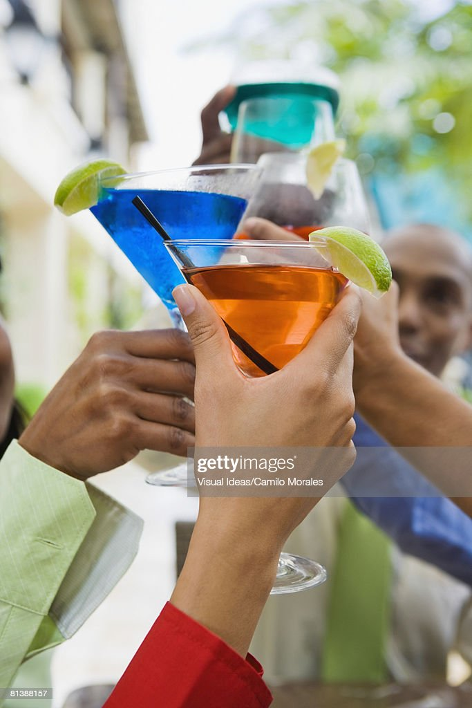 Hispanic friends toasting with cocktails : Stock Photo