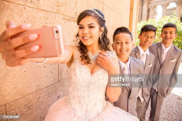 Hispanic girl and boys posing for cell phone selfie