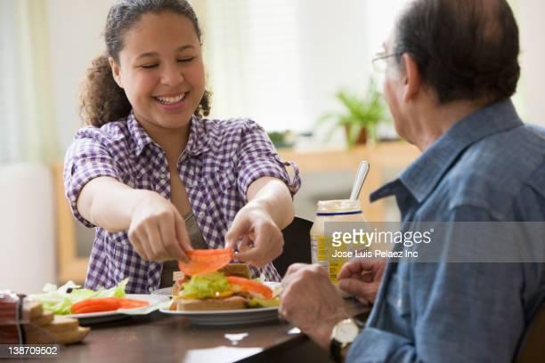 Hispanic girl and grandfather making sandwich