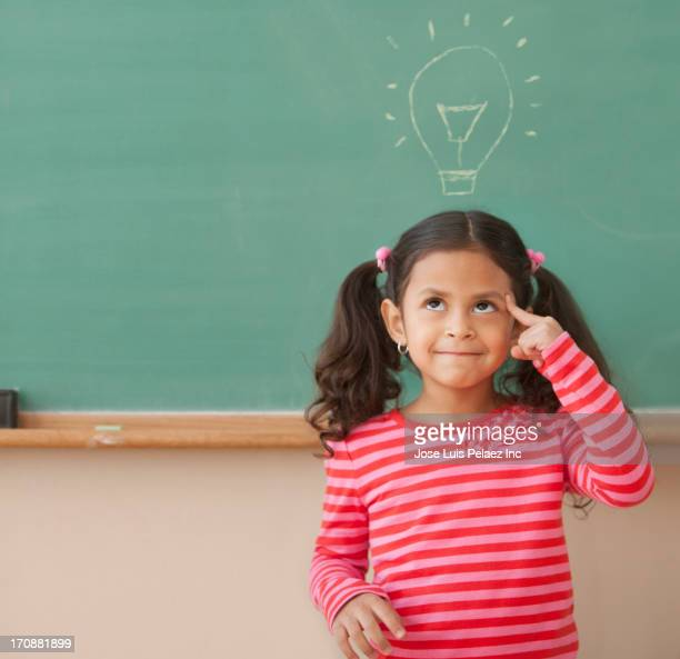 Hispanic girl at chalkboard with light bulb over head