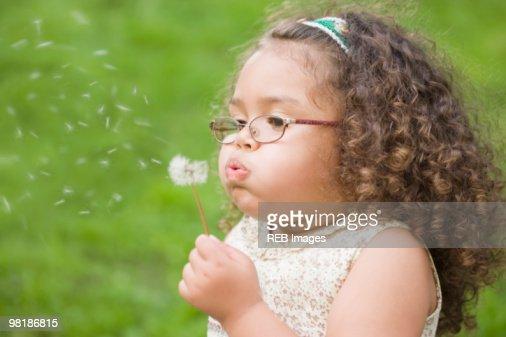 Hispanic girl blowing dandelion : Stock Photo