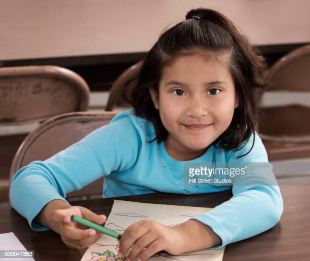 Hispanic girl coloring at desk