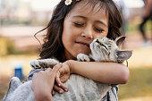 Hispanic girl cradling cat