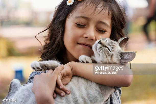 Hispanic girl cradling cat