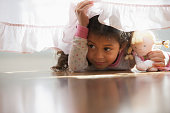 Hispanic girl crawling under bed