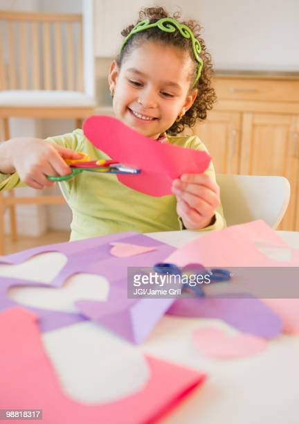 Hispanic girl cutting construction paper