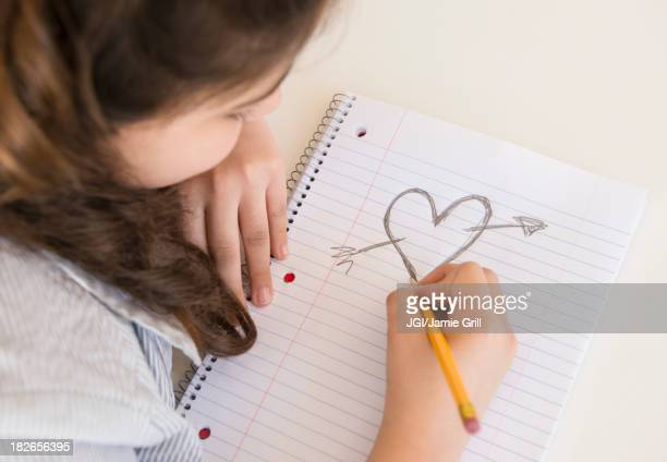 Hispanic girl doodling heart and arrow