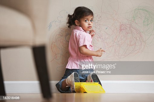 Hispanic girl drawing on wall
