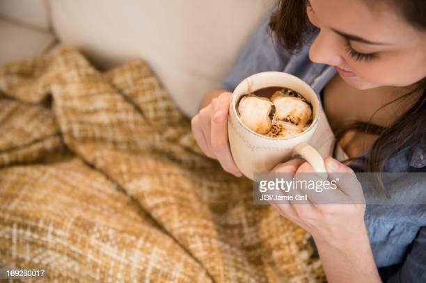Hispanic girl drinking hot chocolate