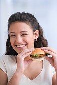 Hispanic girl eating hamburger