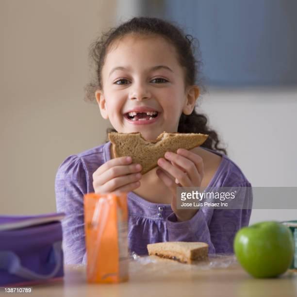 Hispanic girl eating lunch at school