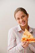 Hispanic girl eating slice of pizza