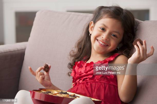 Hispanic girl eating Valentine's chocolate on sofa