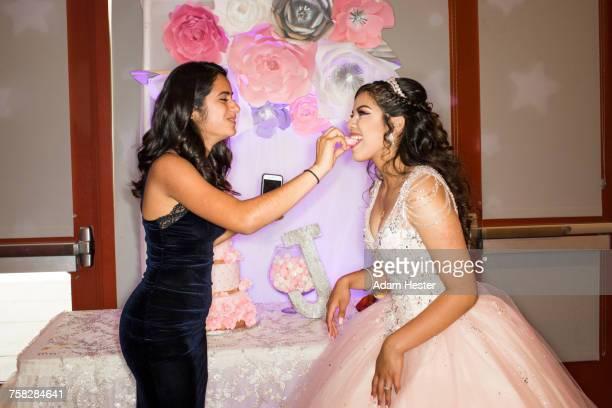 Hispanic girl feeding cookie to friend