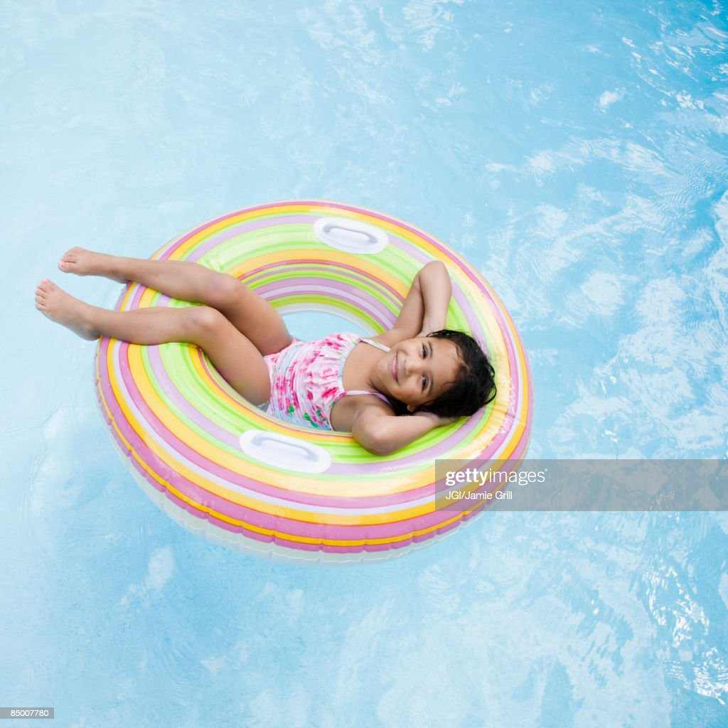 Hispanic girl floating in pool in inflatable ring
