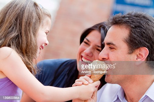 Hispanic girl giving father a bite of her ice cream cone : Stock Photo