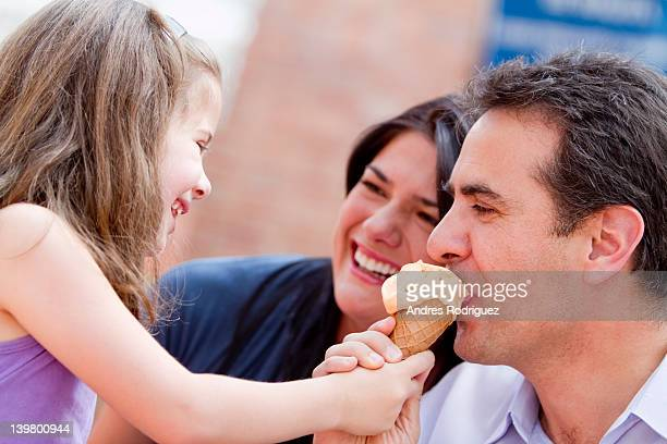 Hispanic girl giving father a bite of her ice cream cone