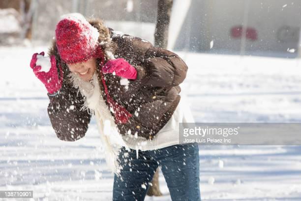 Hispanic girl having snowball fight