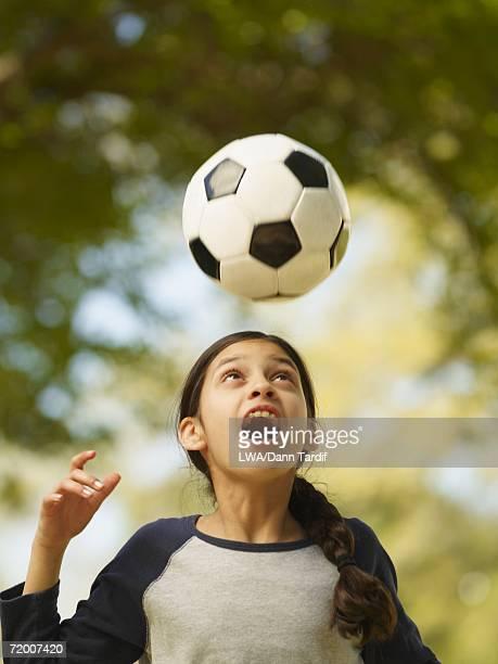 Hispanic girl hitting soccer ball with head