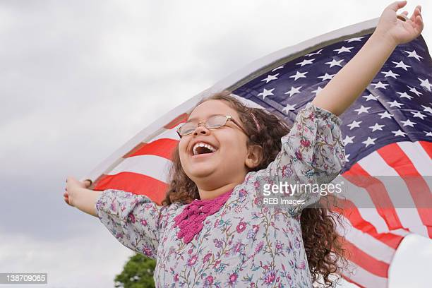 Hispanic girl holding American flag with arms raised