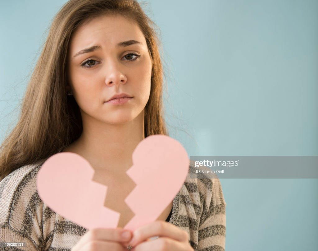 Hispanic girl holding broken heart shape : Stock Photo
