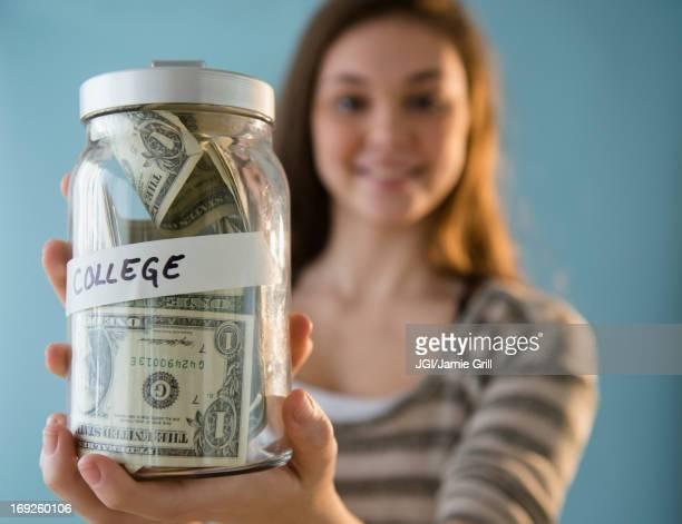 Hispanic girl holding â'college' savings jar