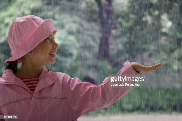 Hispanic girl holding hand out in rain