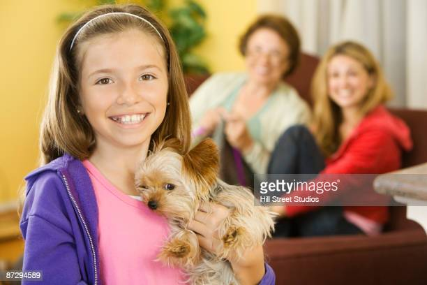 Hispanic girl holding pet dog