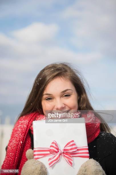 Hispanic girl holding present in snow