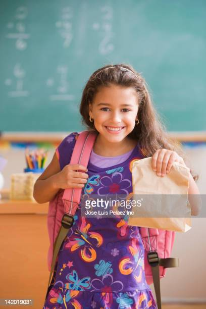 Hispanic girl holding sack lunch in classroom