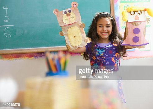 Hispanic girl holding sack puppets in classroom